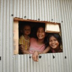 Some girls looking at me through the window of their living room in Kampot province.